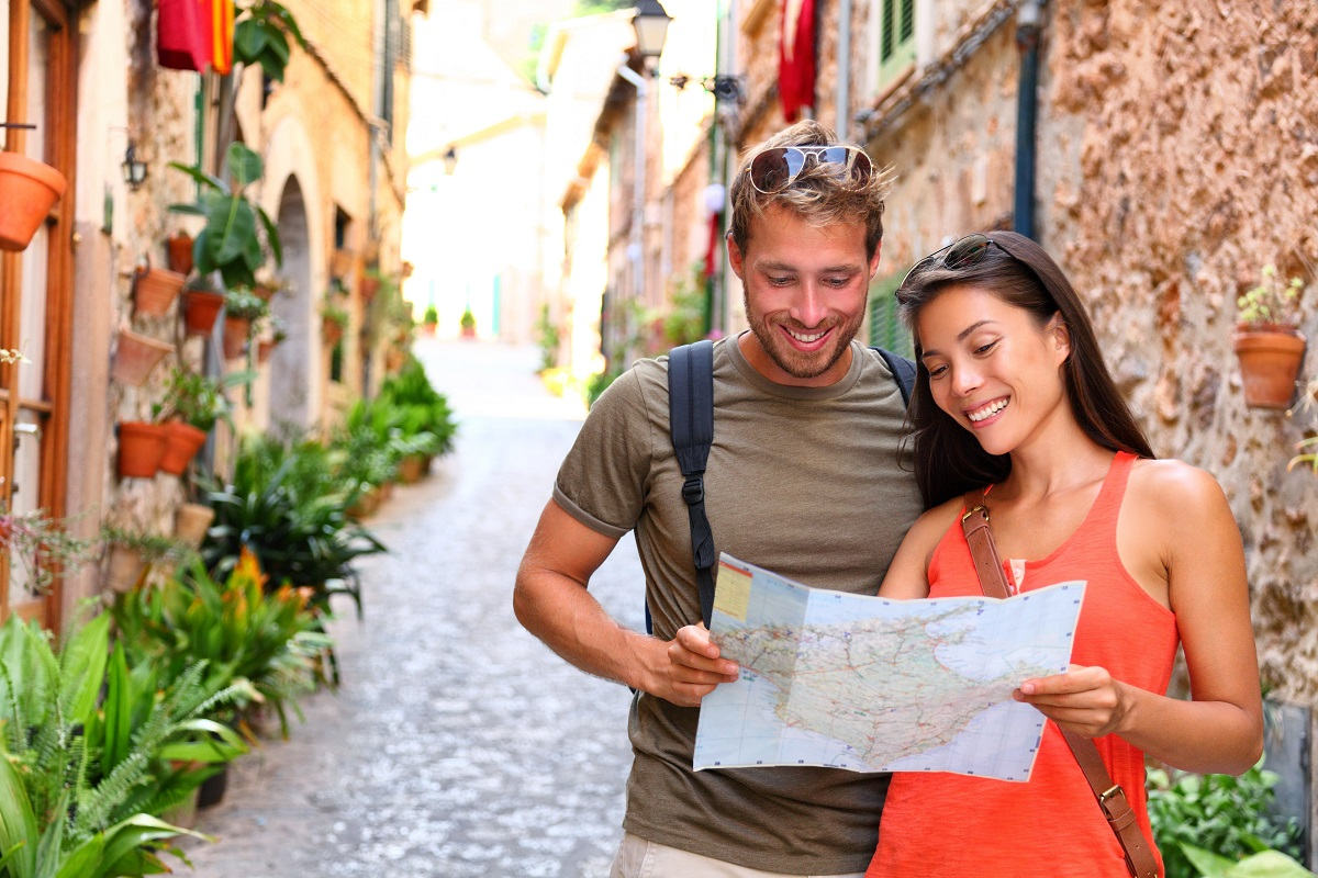 tourists couple looking at map to find directions walking in old streets
