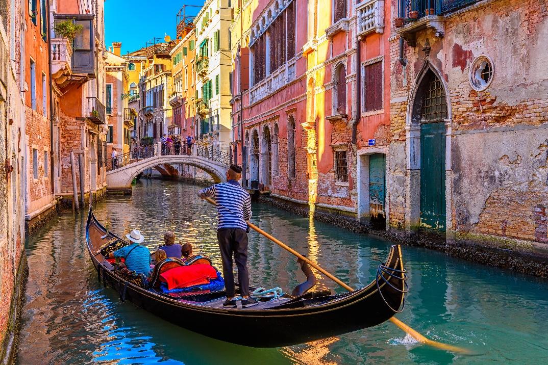 narrow canal with gondola and bridge in venice, Italy