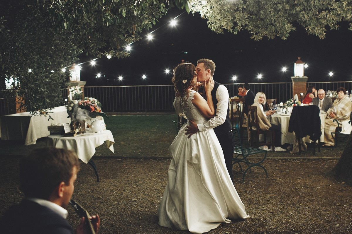 Groom hugs bride tender while they dance on the backyard in the evening
