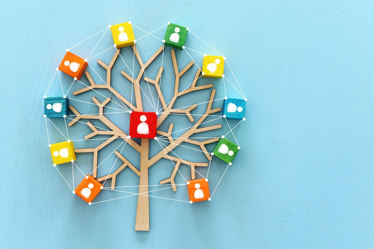 Business image of wooden tree with people icons over blue table