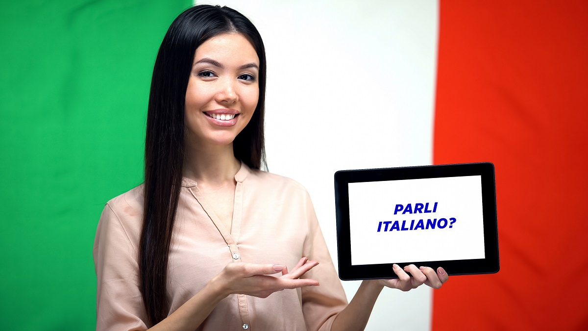 Woman holding tablet with do you speak italian phrase, app for learning language