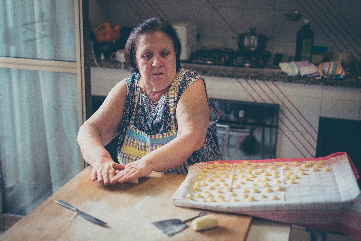 italian woman make homemade pasta gnocchi on wood board