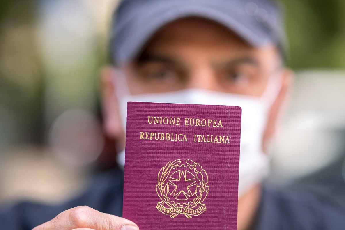 Tourist wearing a medical protective mask showing to the camera his Italian passport