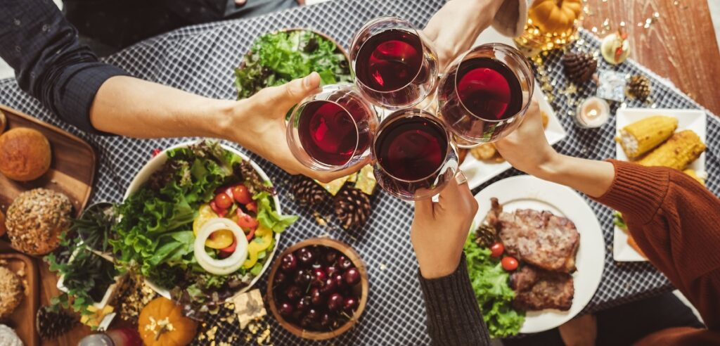 Group of young people celebrating Christmas thanksgiving party dinner with clinking glass of wine