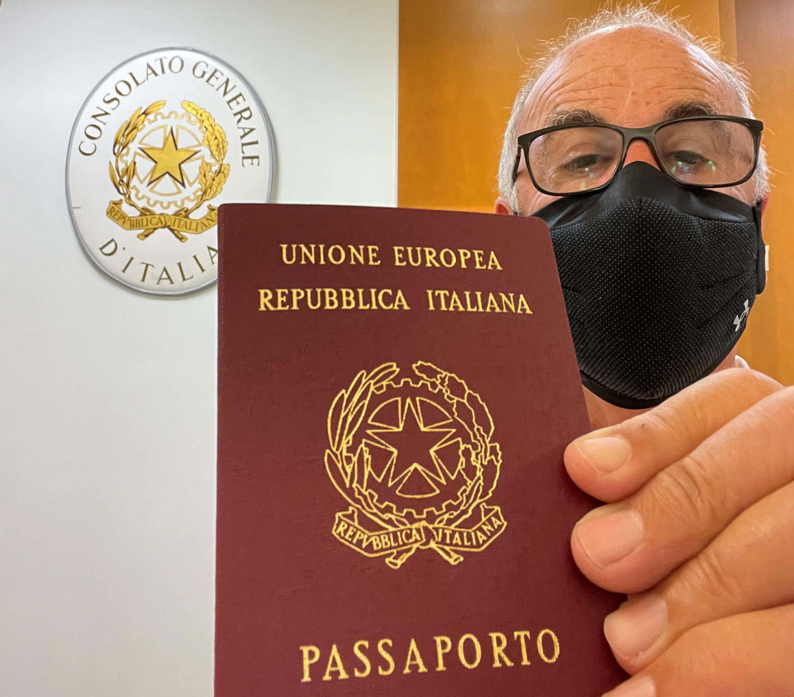 Man with mask holding Italian passport