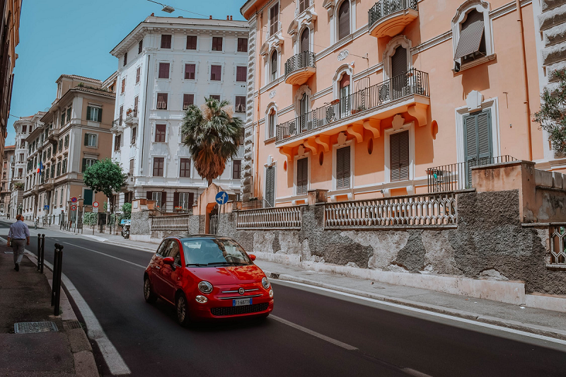Red hatchback car on a narrow street with apartment buildings